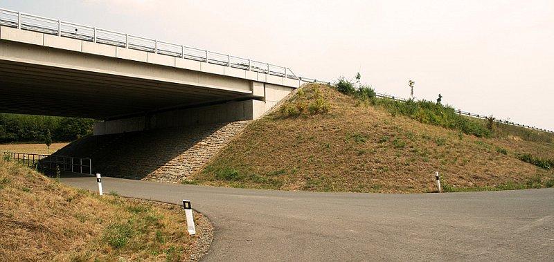 Podjezd pod dálničním mostem a pak doprava a do kopce.